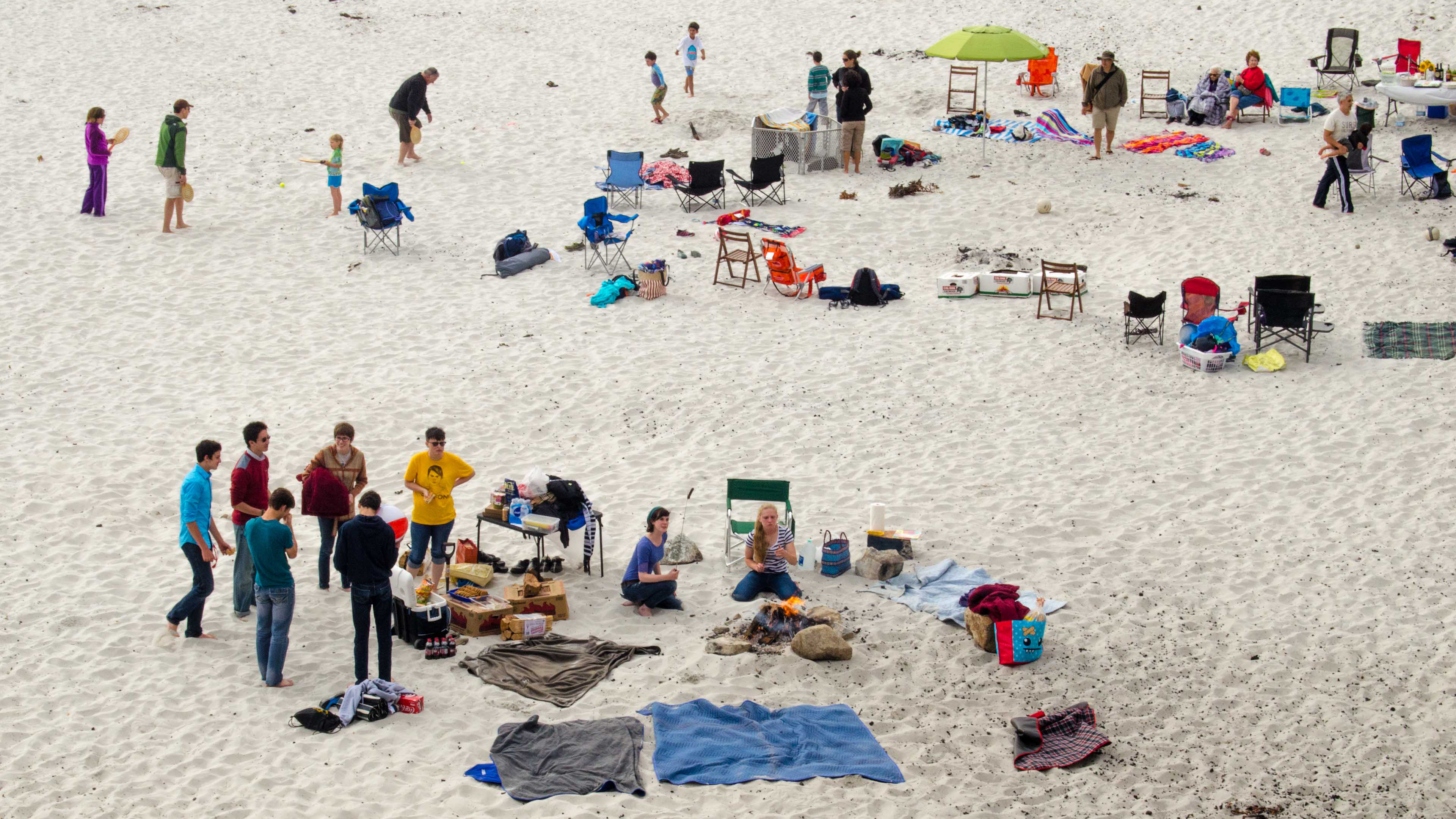 People gathering on the beach eating marshmallows